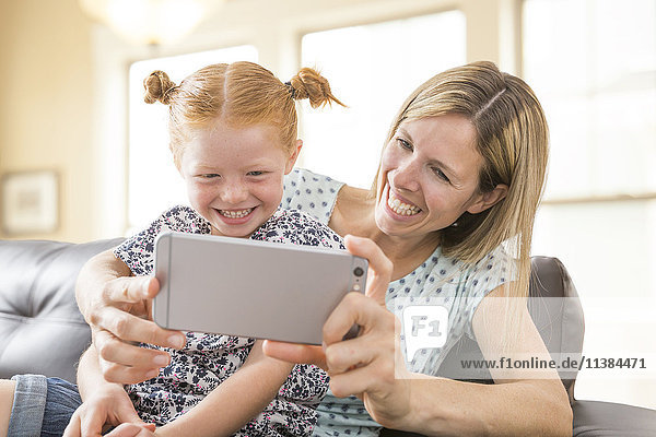 Caucasian mother and daughter posing for cell phone selfie