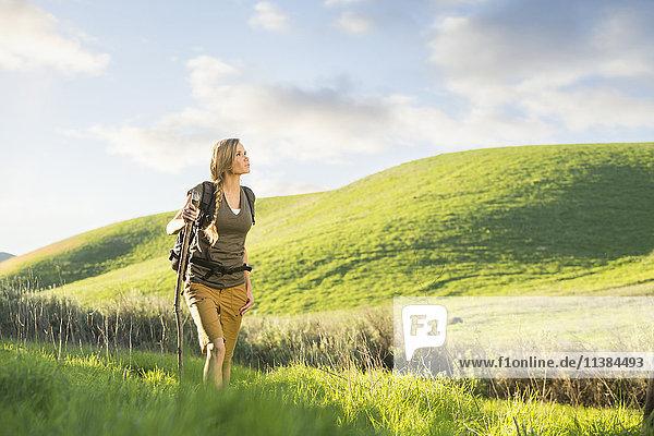 Caucasian woman holding walking stick on hill