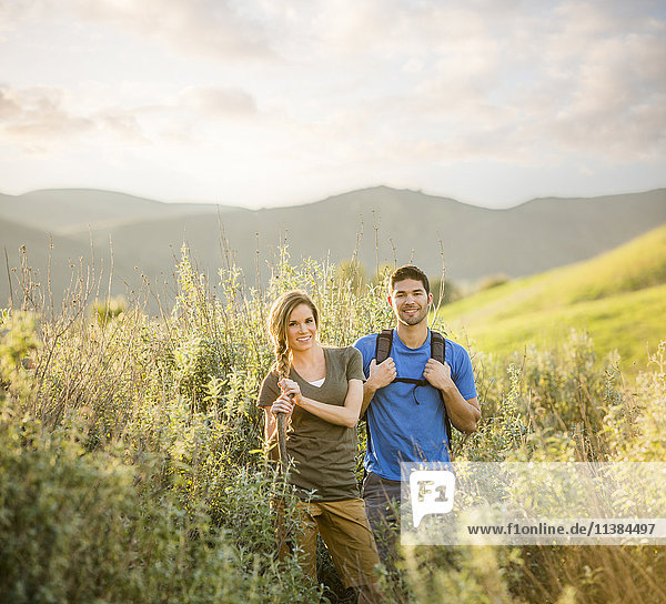 Portrait of Caucasian couple hiking on hill