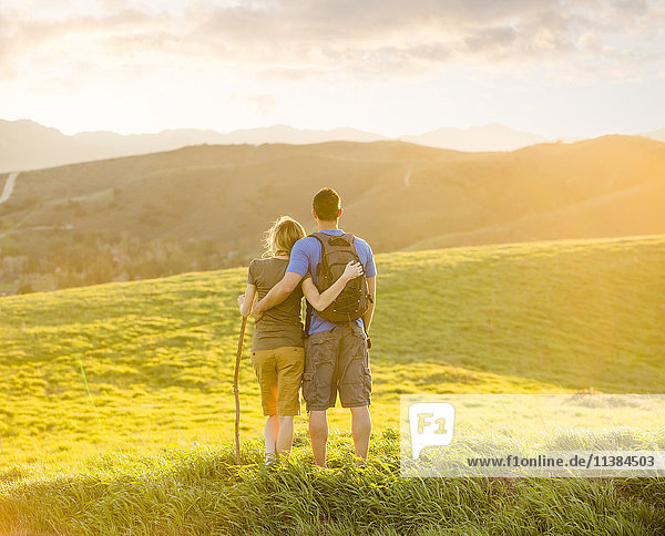 Caucasian couple hugging on hill