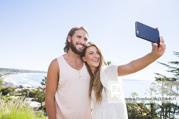 Caucasian couple posing for cell phone selfie at beach