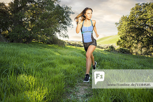 Caucasian woman running on hill