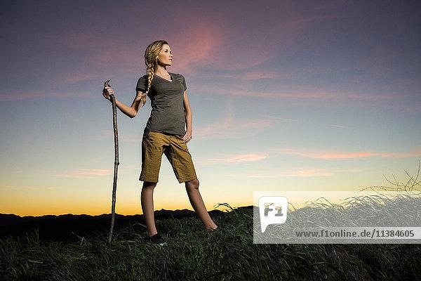 Caucasian woman holding walking stick at sunset