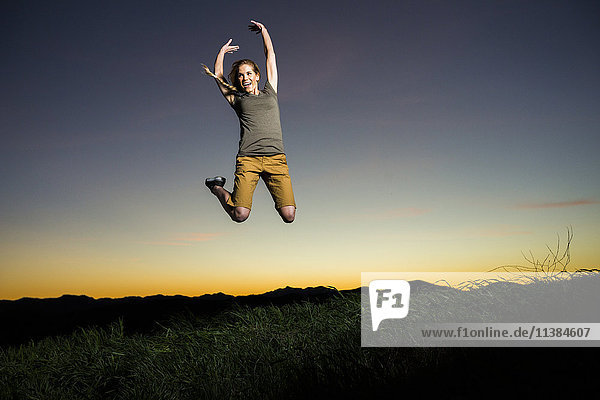 Caucasian woman jumping for joy at sunset