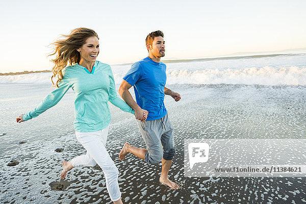 Couple holding hands running on beach