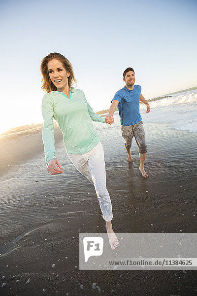 Couple holding hands running on beach