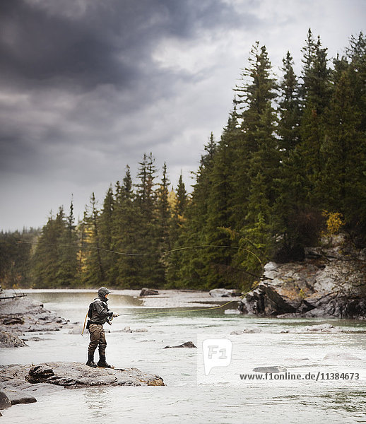Caucasian man fishing at river