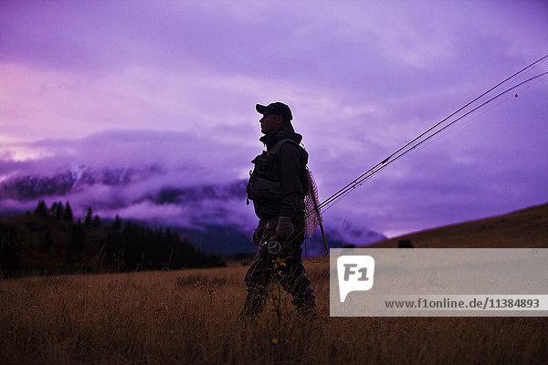 Caucasian man walking and carrying fishing rods