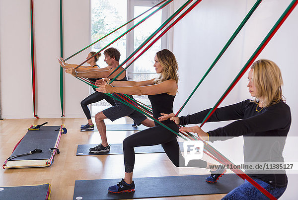 People pushing on resistance bands in gymnasium