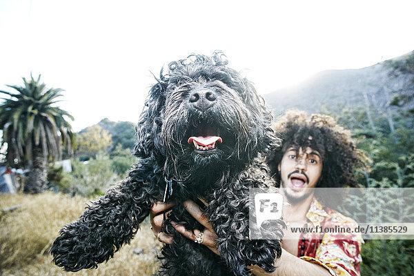 Mixed Race man holding shaggy dog Mixed Race man holding shaggy dog