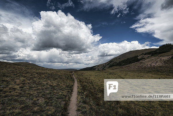 Clouds over trail in rolling landscape