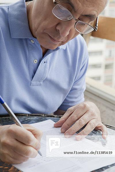 Hispanic man writing on paperwork