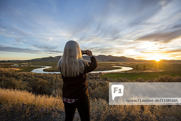 Caucasian woman photographing sunset over winding river