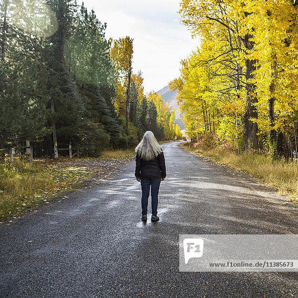 Caucasian woman standing in road near trees
