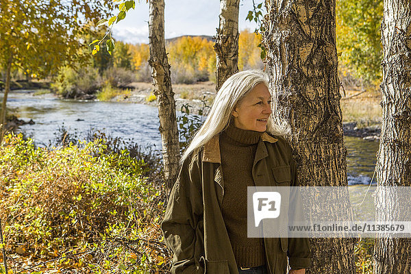 Smiling Caucasian woman leaning on tree near river