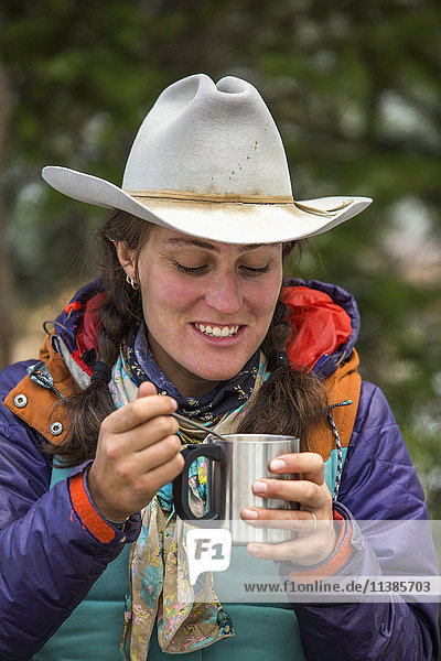 Caucasian woman using spoon with metal cup in winter