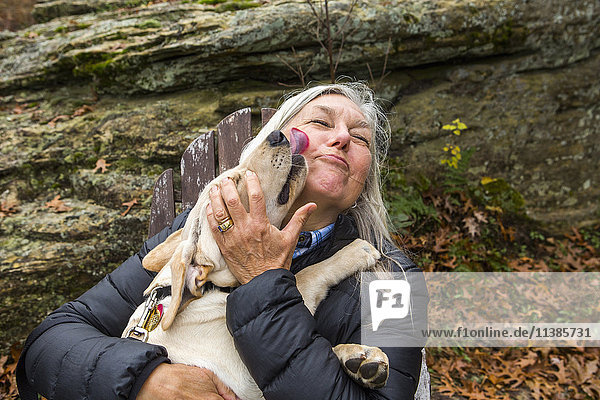 Dog licking face of Caucasian woman outdoors