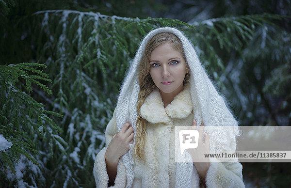 Caucasian woman wearing fur coat in snowy forest
