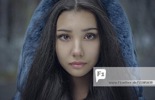 Portrait of serious Mixed Race teenage girl wearing blue hood