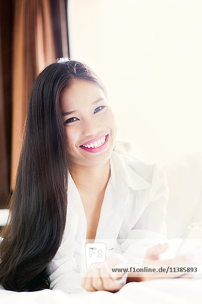 Portrait of smiling Asian teenage girl laying on bed