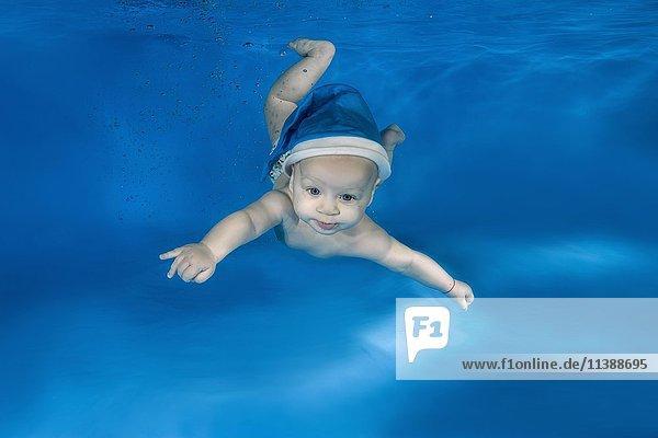 Baby  Junge  mit blauer Santa-Mütze  schwimmt unter Wasser in einem Pool  Odessa  Ukraine  Europa