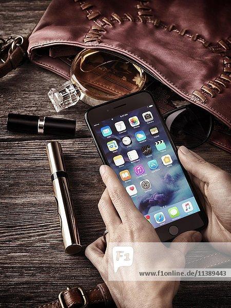 Frauenhände halten ein Apple iPhone 7 Plus  mit Handtasche  Make-up und Accessoires auf dem Tisch  Stillleben