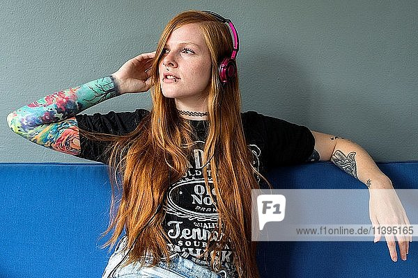 Tilburg  Netherlands. Young red haired woman listening to her music  uploaded on her smartphone  while relaxing on her living room couch.