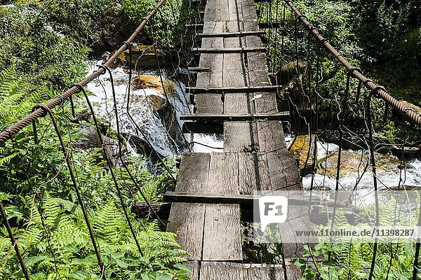 Alte hölzerne Hängebrücke über kleinem Fluss im oberen Modi Khola Tal  Landruk  Kaski  Nepal  Asien