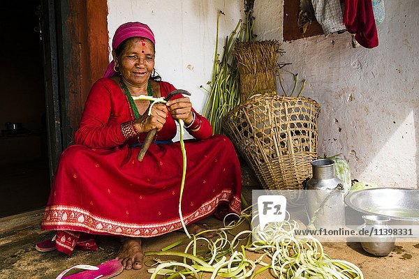Einheimische Frau schneidet Gemüse vor einem Bauernhaus  Tollogau  Kaski Distrikt  Nepal  Asien