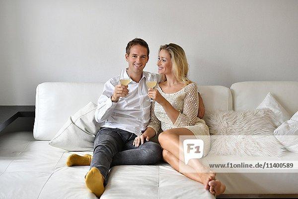 Mann  Frau  Pärchen auf Sofa  verliebt  Wein  Glas  Blick in die Kamera