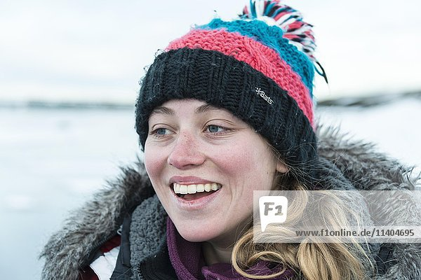 Young woman wearing woolly hat  laughing  portrait  Fjallsárlón Glacier Lagoon  Iceland  Europe
