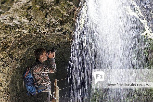 Junger Mann fotografiert hinter Wasserfall  Partnachklamm  Oberbayern  Bayern  Deutschland  Europa