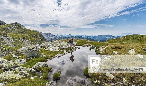 Wanderin an einem kleinen Bergsee mit Alpenpanorama  Schladminger Tauern  Schladming  Steiermark  Österreich  Europa