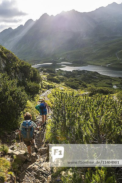 Two hikers on a trail in the morning  Giglachseen  Schladming Tauern  Schladming  Styria  Austria  Europe