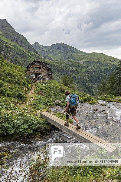 Wanderin überquert Holzbrücke über Gebirgsbach  Gollinghütte  Rohrmoos-Untertal  Schladminger Tauern  Steiermark  Österreich  Europa