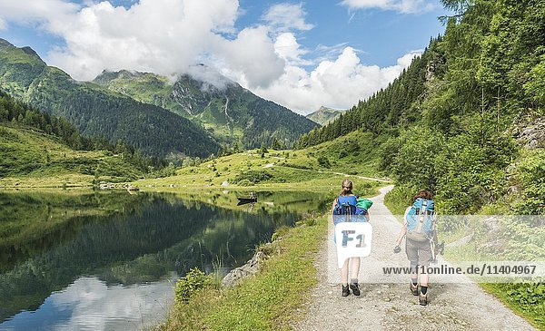 Zwei Wanderer auf einem Forstweg  Riesachsee  Rohrmoos-Untertal  Schladminger Tauern  Schladming  Steiermark  Österreich  Europa