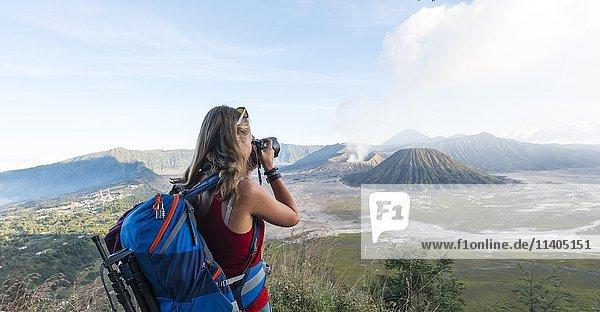 Touristin mit Kamera  rauchender Vulkan Gunung Bromo  vorne Mt. Batok  hinten Mt. Kursi  Mt. Gunung Semeru  Nationalpark Bromo-Tengger-Semeru  Java  Indonesien  Asien