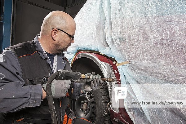 Car bodywork  worker fixing a dent  sheet metal damage on a car fender  Germany  Europe