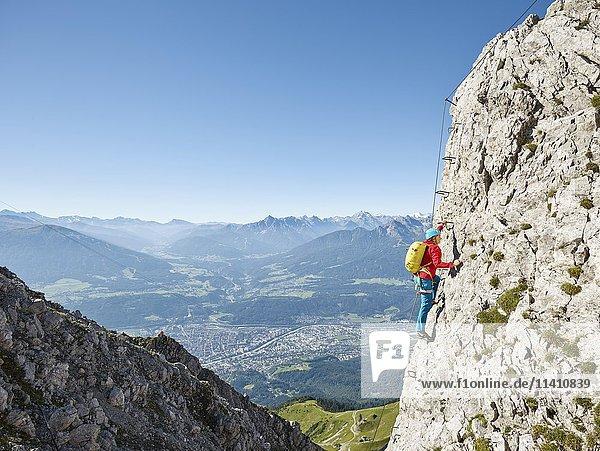 Nordkette Innsbruck Klettersteig  Kletterin am Stahlseil gesichert steigt über Eisenleiter auf  Nordkette Innsbruck  Tirol  Österreich  Europa