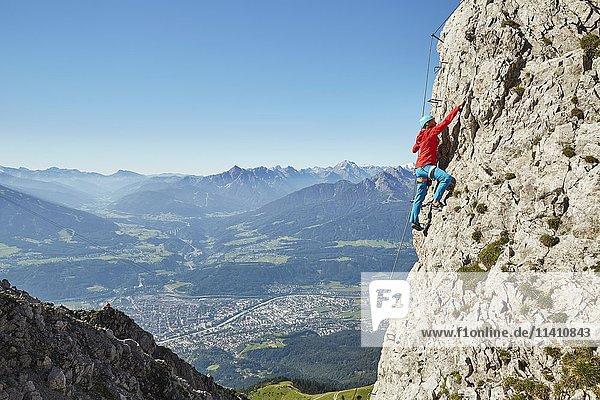 Nordkette Klettersteig  Kletterin am Stahlseil gesichert steigt über Eisenleiter auf  Nordkette Innsbruck  Tirol  Österreich  Europa