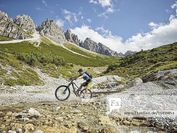 Mountainbiker fährt mit seinem Mountainbike durch einen Bach  hinten Bergkette Kalkkögel  Stubaier Alpen  Tirol  Österreich  Europa