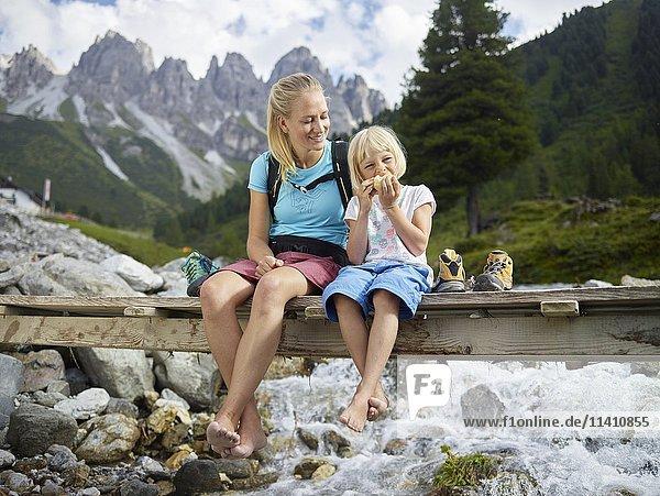 Frau 25-30 Jahre blonde Haare sitzt mit ihrer Tochter auf einer Brücke  Kemater Alm  Tirol  Österreich  Europa