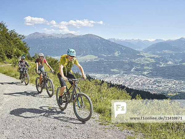 Family on mountain bikes  dirt road  Innsbruck behind  Inn Valley  Tyrol  Austria  Europe