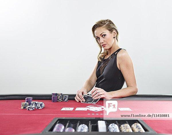 Frau spielt Black Jack  verführerischer Blick  Spielkarten  Jetons  Casino