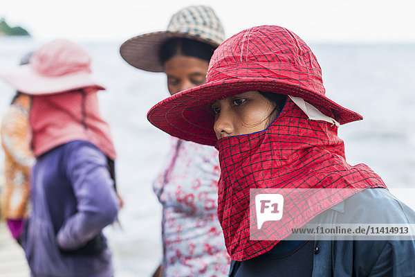 'Women wearing hats and scarves covering their mouths  local life in the famous Crab Market; Kep  Cambodia'