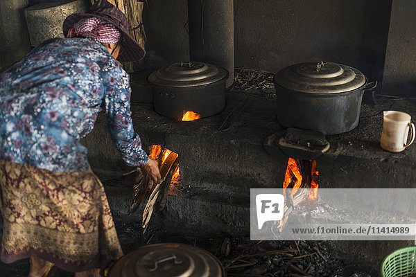 'A woman puts firewood into the flames under pots  local life in the famous crab market; Kep  Cambodia'