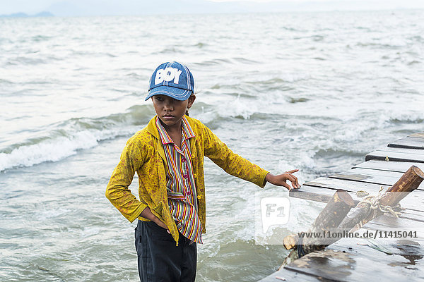 'A boy stands in the water at the edge of the dock  local life in the famous crab market; Kep  Cambodia'