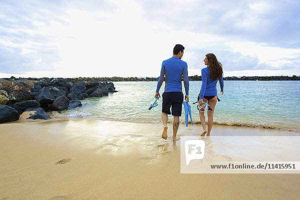 'A couple walks into the water from Lydgate Beach holding flippers and snorkeling gear; Kauai  Hawaii  United States of America'