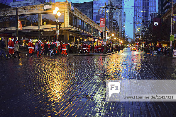 'The Drunk santas Christmas party  a traditional annual gathering of hundreds of jolly Christmas revelers bar hopping through downtown Seattle including making a stop at the world famous Pike Place Public Market; Seattle  Washington  United States'