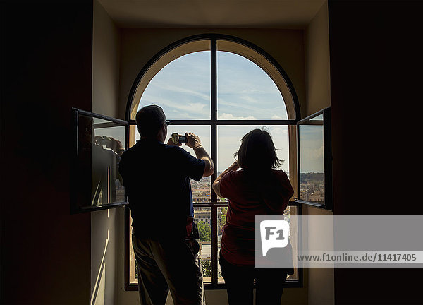'Tourists taking photographs from a window inside The Vatican; Rome  Italy'